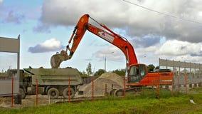 A cubeta da máquina escavadora carrega o caminhão pesado com a terra filme