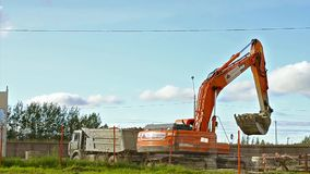 A cubeta da máquina escavadora carrega o caminhão pesado com a terra video estoque
