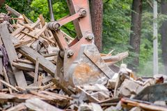 A cubeta da máquina escavadora carrega restos de construção após a demolição da construção velha fotografia de stock