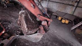 A cubeta da máquina escavadora da construção com grande interior da pedra está acima, construtores está andando abaixo em uma áre vídeos de arquivo