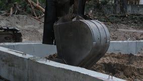 A cubeta da máquina escavadora escava a terra video estoque