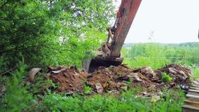 A cubeta da máquina escavadora escava a terra com restos filme