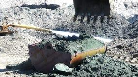 A cubeta da máquina escavadora espalha o volume do solo em um recipiente do ferro filme