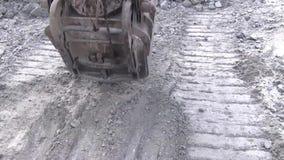 A cubeta da máquina escavadora está balançando acima da terra filme