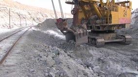 A cubeta da máquina escavadora move-se acima da estrada de ferro filme