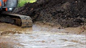 Cubeta da máquina escavadora para tirar a água na vala inundada em um canteiro de obras para o reparo da estrada video estoque