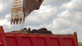 Cubeta da máquina escavadora que está sendo despejada no caminhão basculante vídeos de arquivo