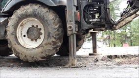 Cubeta da máquina escavadora, que nivelou a terra à vista da asfaltagem da estrada filme