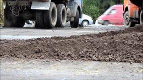 Cubeta da máquina escavadora, que nivelou a terra à vista da asfaltagem da estrada video estoque
