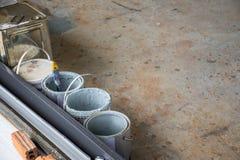 A cubeta da pintura é já assoalho concreto sobre posto uso no constru imagens de stock