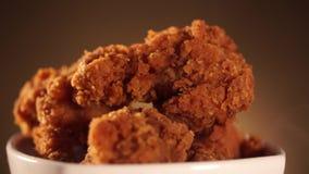 Cubeta da rotação completamente do frango frito friável de kentucky com fumo no fundo marrom vídeos de arquivo