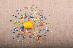 A cubeta de seixos coloridos derrama no fundo da lona Imagem de Stock Royalty Free