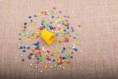 A cubeta de seixos coloridos derrama no fundo da lona Foto de Stock Royalty Free