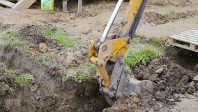 A cubeta de terraplenagens de escavação de uma máquina escavadora mecânica em um canteiro de obras video estoque