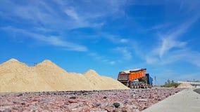 A cubeta do trator carrega o caminhão pesado com a areia filme