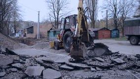 A cubeta do trator quebra o asfalto filme