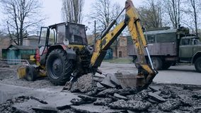 A cubeta do trator quebra o asfalto vídeos de arquivo