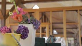 A cubeta esmaltada com rosas brancas está sendo levada embora da tabela pelo florista fêmea novo vídeos de arquivo