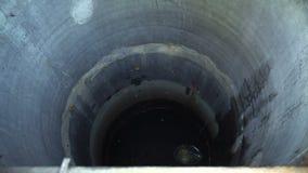 A cubeta galvanizada deixa cair e aumenta com no bem para obter uma água filme