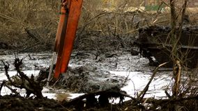 A cubeta larga da máquina escavadora escava acima o solo da parte inferior do rio Limpeza e aprofundamento do canal video estoque