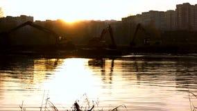 A cubeta larga da máquina escavadora escava acima o solo da parte inferior do rio Limpeza e aprofundamento do canal filme