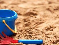 A cubeta plástica e o ancinho da criança na areia Fotos de Stock