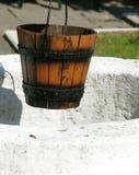 Cubeta vazia que pendura sobre um poço antigo Fotografia de Stock Royalty Free