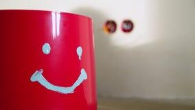 Cubeta vermelha com a cara no concreto no canteiro de obras filme