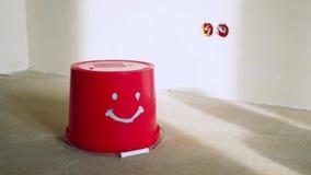 Cubeta vermelha com a cara no concreto no canteiro de obras video estoque