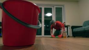 Cubeta vermelha e homem defocused no tshirt vermelho que limpa a sala tiro 4k filme