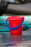 Cubeta vermelha e mangueira verde Fotos de Stock Royalty Free