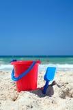 Cubeta vermelha e pá azul na praia ensolarada, arenosa Fotos de Stock Royalty Free