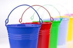 Cubetas coloridas na linha imagens de stock