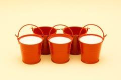 Cubetas vermelhas com leite em um amarelo Fotos de Stock Royalty Free