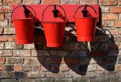3 cubetas vermelhas da emergência que penduram em uma parede fotos de stock royalty free