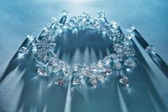 Cubetti di ghiaccio brillanti sotto forma di struttura rotonda su un fondo blu immagine stock libera da diritti