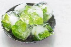 Cubetti di ghiaccio casalinghi con le foglie di menta dentro su di piastra metallica, su ghiaccio per limonata e sul cocktail, or Fotografie Stock Libere da Diritti