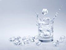 Cubetti di ghiaccio che cadono in acqua Immagini Stock Libere da Diritti