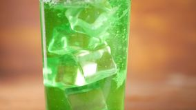 Cubetti di ghiaccio che cadono in acqua verde scintillante video d archivio
