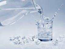 Cubetti di ghiaccio che cadono in un'acqua Immagini Stock Libere da Diritti