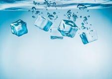 Cubetti di ghiaccio che rientrano nell'acqua Immagini Stock