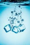 Cubetti di ghiaccio che rientrano nell'acqua Fotografia Stock