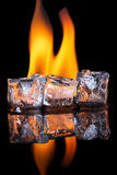 Cubetti di ghiaccio con la fiamma sulla superficie brillante del nero Fotografia Stock