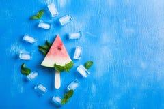 Cubetti di ghiaccio delle foglie di menta del ghiacciolo dell'anguria sul backgro di legno blu immagine stock libera da diritti