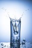 Cubetti di ghiaccio di caduta in un bicchiere d'acqua con spruzzata Fotografia Stock Libera da Diritti