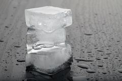 Cubetti di ghiaccio sul fondo nero della tavola fotografie stock