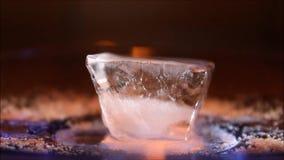 Cubetto di ghiaccio bruciante nel primo piano scuro Immagini Stock