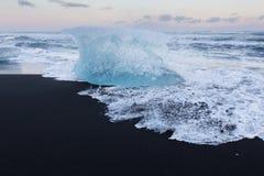 Cubetto di ghiaccio che tagliato sulla spiaggia di sabbia nera Immagine Stock