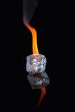 Cubetto di ghiaccio con la fiamma sulla superficie brillante del nero Immagini Stock