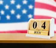 Cubez le calendrier de forme pour le 4 juillet sur la table en bois Image libre de droits